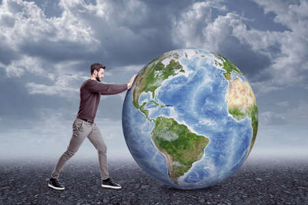 Full length side view of young man in casual clothes pushing big Earth globe on gloomy cloudy day.