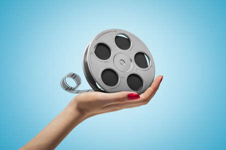 Side closeup of womans hand holding film reel on light blue gradient background.