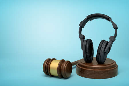 3d rendering of black headphones standing upright on sounding block with judge gavel beside on light-blue background. 写真素材