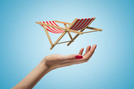 Side closeup of womans hand facing up and levitating small striped chaise-longue on light blue gradient background.