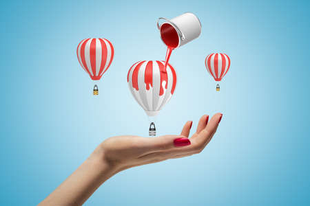 Three small hot-air balloons above womans hand on light blue background and paint can in air pouring red paint on central balloon.