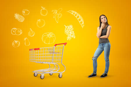 Young thinking brunette girl wearing casual jeans and t-shirt with shopping cart and cartoon food drawn on yellow background