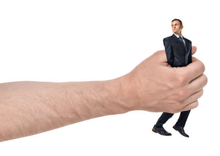Side close-up of big mans hand holding small businessman isolated on white background.