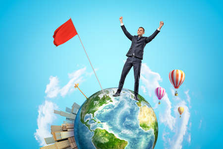 Small planet Earth with modern city popping up on one side and hot-air balloons flying in sky, and happy businessman who has planted red flag on planet