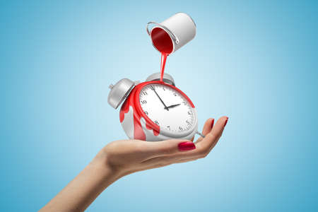 Female hand holding alarm clock with red paint bucket turned upside down above it on blue background Zdjęcie Seryjne