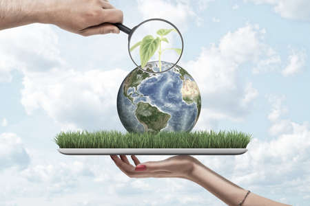 Magnifying glass in mans hand zooming at green sprout on small planet Earth lying on screen of digital tablet that is resting on womans palm. Stok Fotoğraf