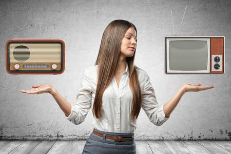 Bild der jungen schönen Geschäftsfrau zuschneiden, Hände an den Seiten, Handflächen nach oben, schwebendes Retro-Radio und veraltetes Fernsehgerät.