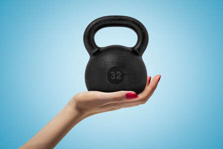 Side closeup of womans hand facing up and holding big black 32 kg kettlebell on light blue gradient background.