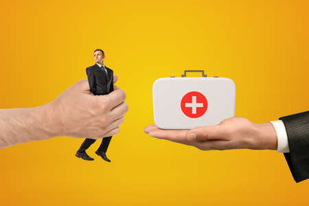 Mans hand exchanging tiny businessman for medical bag held in another mans hand on amber background. Stock fotó