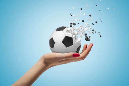 Side closeup of womans hand facing up and holding football that has started to break into small pieces on light blue background.