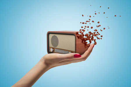 Female hand holding old radio set shattering into pieces on blue background