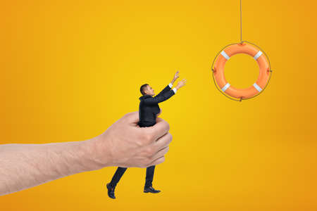Big male hand holding businessman reaching out to orange boat lifebuoy on yellow background