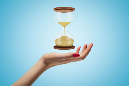 Side closeup of womans hand facing up and levitating hourglass on light blue background.