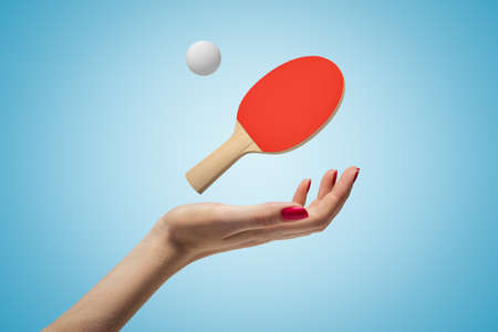 Female hand with ping pong racket and ball above on blue background Stock fotó