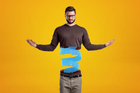 Young man in casual clothes cut in half with blue liquid spiral inside on yellow background Zdjęcie Seryjne