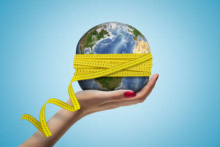 Female hand holding Earth globe covered with yellow measuring tape on blue background Zdjęcie Seryjne