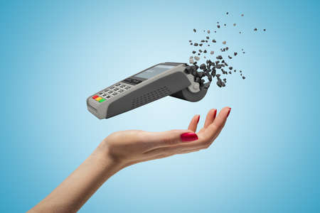 Closeup of womans hand levitating point-of-sale terminal which has started to break into small pieces on light blue background. Imagens