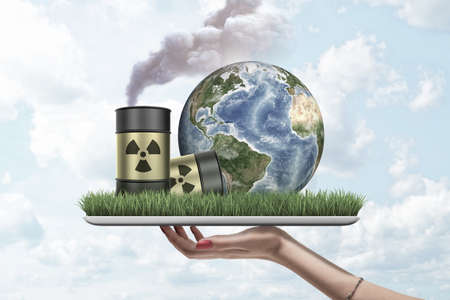Womans hand holding digital tablet with green grass, planet Earth and two radioactive waste barrels placed on screen, against cloudy sky.