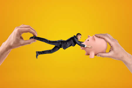 Big male hand holding tiny businessman who is reaching to another big hand holding pink piggy bank on yellow background