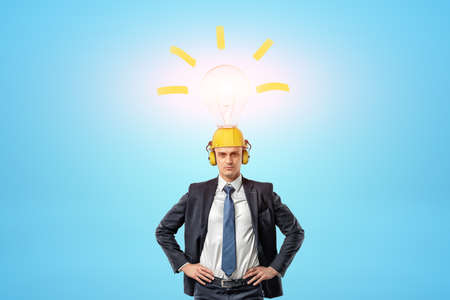 Businessman wearing yellow safety helmet with light bulb above on blue background