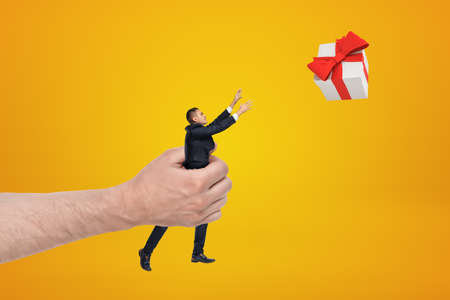 Big male hand holding businessman reaching out to gift box on yellow background Banco de Imagens