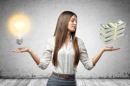 Crop image of young beautiful businesswoman, hands at sides, palms facing up and levitating light bulb and stack of cash. 免版税图像