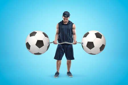 Strong muscular young man holding bar-bell with two football balls on blue background