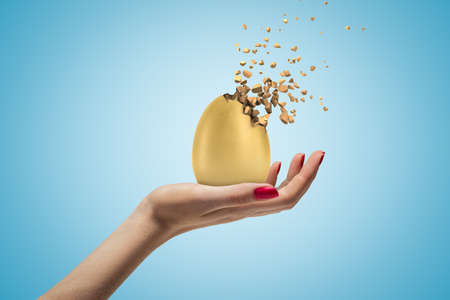Female hand holding golden egg shattering into pieces on blue background