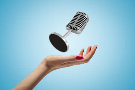 Side closeup of woman hand facing up and levitating microphone on light blue gradient background.