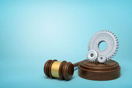 3d rendering of one big and two small light-grey gear wheels on sounding block with gavel lying beside on light-blue background with copy space.