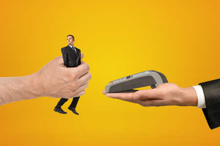 Big male hand passing tiny businessman to another hand with PIN pad on yellow background