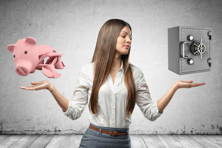 Crop image of young attractive businesswoman, hands at sides, levitating locked money vault and broken piggy bank in air.