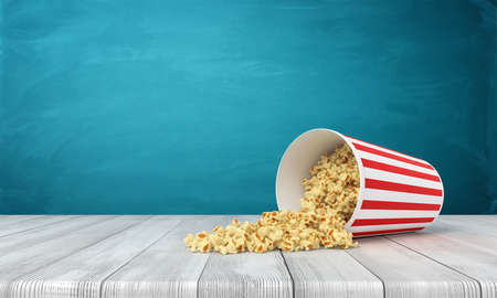 3d rendering of popcorn bucket lying sidelong with some popcorn spilled on wooden surface near blue wall with copy space. Banco de Imagens