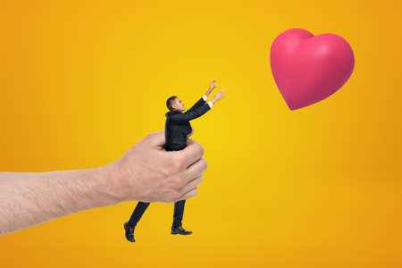 Big hand holding small businessman reaching out with his both hands for red valentine heart on amber background. Banco de Imagens