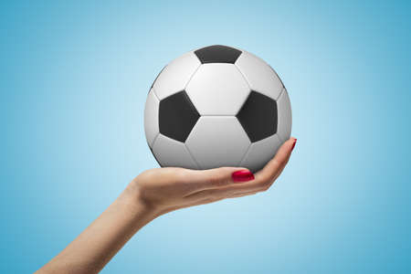 Side closeup of woman hand facing up and holding new football on light blue background.