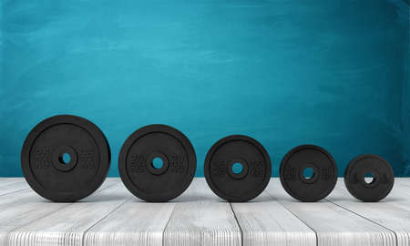 3d rendering of five black weight plates on white wooden floor and dark turquoise background Banco de Imagens