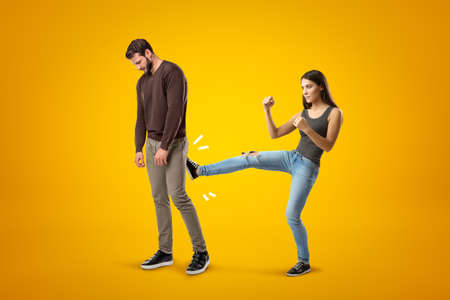Young brunette girl wearing casual jeans and t-shirt kicking sad young man in casual clothes on yellow background