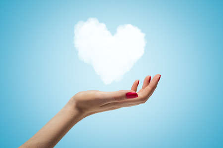 Side closeup of womans hand facing up and levitating small white heart-shaped cloud on light blue gradient background. Banco de Imagens