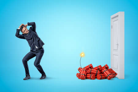 Businessman protecting himself with hands and red dynamite sticks with lit fuse next to white doorway on blue background