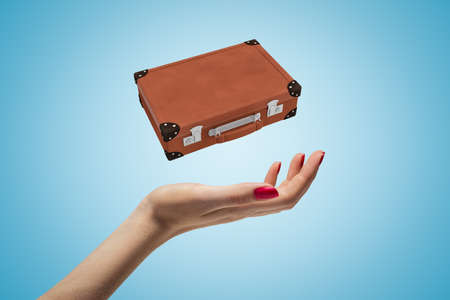 Closeup of womans hand levitating brown travel case on light blue background. Stock fotó