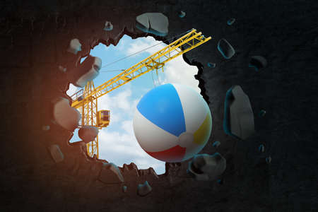 3d rendering of hoisting crane carrying beach ball and breaking hole in black wall with blue sky seen through.