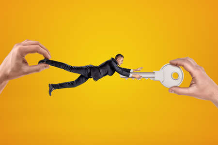 Big male hand holding tiny businessman who is reaching to another big hand holding silver metal key on yellow background