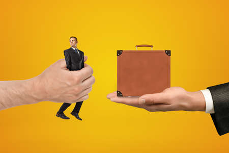Mans hand exchanging tiny businessman for tiny brown travel case held in another mans hand on amber background.