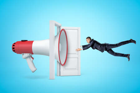 Side view of huge megaphone in open doorway knocking businessman off his feet with sound wave and making him grab at door so as not to fly away. Banco de Imagens
