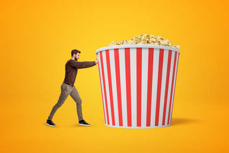 Side view of young man in casual oufit pushing huge bucket of pop corn on amber background. Фото со стока