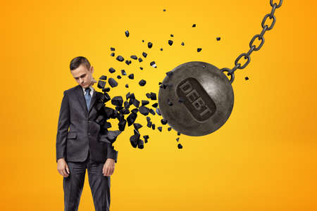 Black wrecking ball with word DEBT on it hitting sad young businessman and breaking half of his body in pieces.