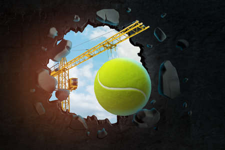 3d rendering of hoisting crane carrying tennis ball and breaking hole in black wall with blue sky seen through. Stok Fotoğraf