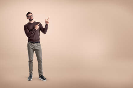 Young smiling man wearing casual clothes and pointing up on beige background