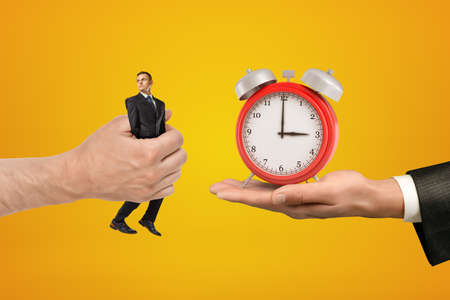 Big male hand passing tiny businessman to another hand with alarm clock on yellow background