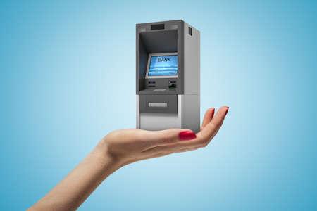 Female hand holding ATM machine on blue background